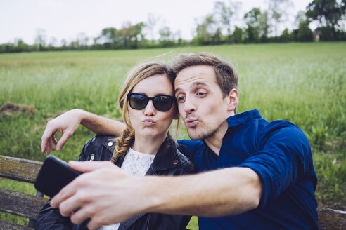 Portrait of couple pouting mouths taking selfie with smartphone - GIOF001004