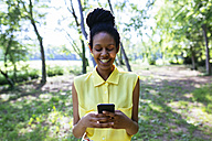 Portrait of smiling young woman in nature looking at her smartphone - GIOF001016