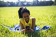 Portrait of young woman with smartphone relaxing on a meadow - GIOF001028