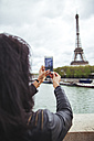 France, Paris, Young woman taking smart phone picture of the Eiffel Tower - ZEDF000118