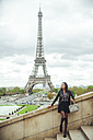 France, Paris, Young woman standing on bridge with theEiffel Tower in background - ZEDF000121
