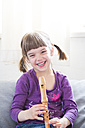 Laughing little girl with recorder at home - LVF004867