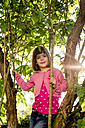 Portrait of little girl climbing in a tree - LVF004871