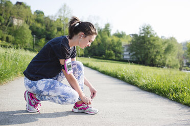 Sportive oung woman tying shoelaces - MRAF000033