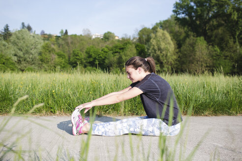 Young woman doing stretching exercises on path in the nature - MRAF000036