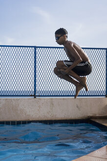 Teenage boy doing a cannonball dive into swimming pool - MAUF000560