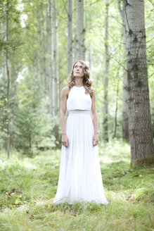 Portrait of young woman wearing white dress in the forest - MAE011706
