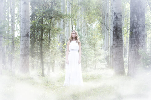 Young woman wearing white dress in the forest - MAE011709
