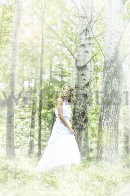 Young woman wearing white dress in the forest - MAE011712
