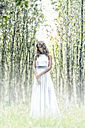 Young woman wearing white dress in the forest - MAE011715