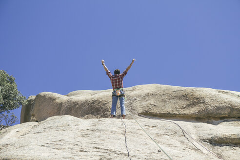 Climber celebrating finishing a climbing route with arms raised - ABZF000518