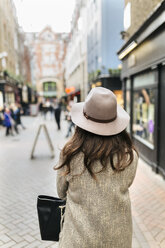 UK, London, back view of young woman on the street - MGOF001820