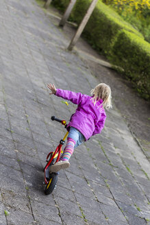 Back view of little girl balancing on her scooter - JFEF000780