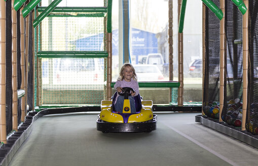 Excited little girl driving bumper car in an indoor playground - JFEF000789