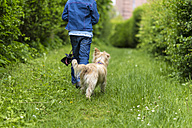 Back view of little girl walking with her dog in nature - JFEF000798