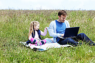 Father and daughter sitting on meadow, smartphone and laptop - MAEF011728