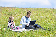 Father and daughter sitting on meadow, smartphone and laptop - MAEF011731