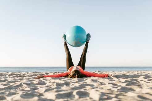Woman doing sports with gym ball early in the morning on the beach - JRFF000671