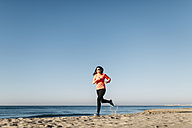 Woman jogging on the beach early in the morning - JRFF000674
