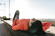 Woman resting, and using the phone after running - JRFF000680