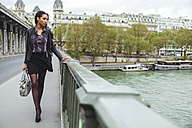 France, Paris, young woman walking on bridge - ZEDF000128