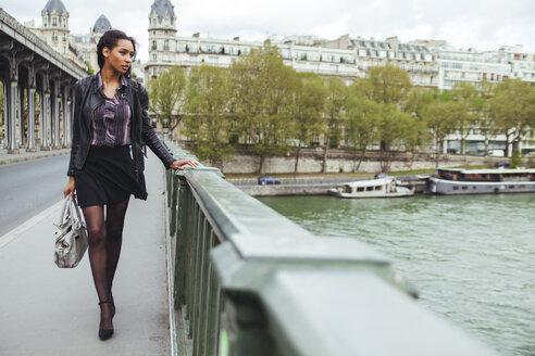 France, Paris, young woman walking on bridge - ZEDF000128
