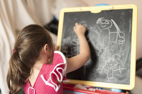 Little girl drawing on chalk board in children's room - JASF000726