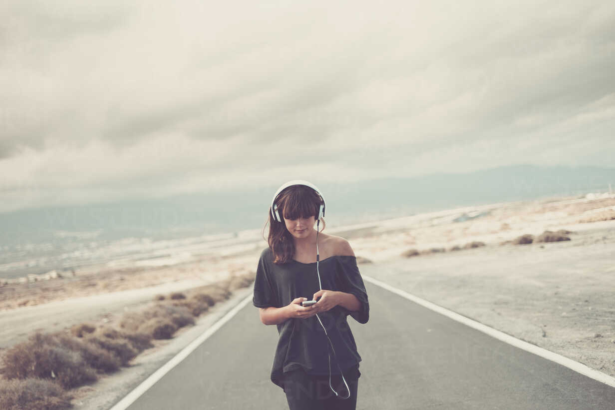 Young woman on the road listening music with headphones - SIPF000471 - Simona Pilolla/Westend61