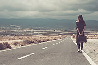 Young woman with suitcase walking on a road - SIPF000480