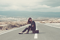 Young woman with suitcase sitting on the road - SIPF000483