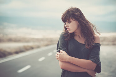 Sad young woman standing on road - SIPF000486