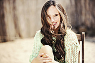 Portrait of smiling young woman with long brown hair - GDF000986