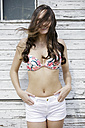 Portrait of smiling young woman with blowing hair wearing bikini top - GDF000989