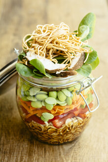 Asian salad in a jar with ramen noodles, red pepper, snow pea pods, carrots, edamame, shiitake mushrooms, salad greens, fried chow mien noodles and dressing - HAWF000898