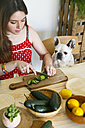 French bulldog watching woman cutting cucumber on table - RTBF000201