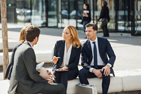 Business colleagues talking outside office building - CHAF001726