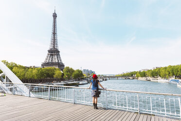 France, Paris, back view of  woman wearing red beret looking at Eiffel Tower - GEMF000894