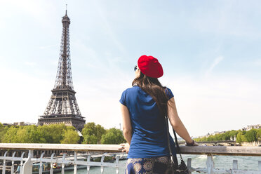 France, Paris, back view of woman wearing red beret looking at Eiffel Tower - GEMF000897