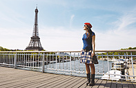 France, Paris, woman wearing red beret standing in front of Seine river and Eiffel Tower - GEMF000900