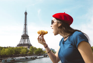 France, Paris, woman eating croissant in front of Seine river and Eiffel Tower - GEMF000903
