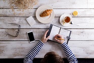 Man working smart phone and personal organiser while having breakfast - HAPF000356