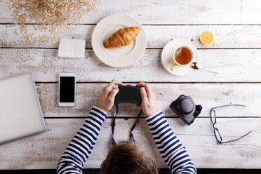 Man working at table with croissant and tea, looking at his camera - HAPF000359