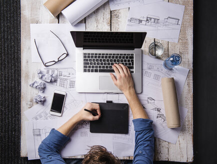 Architect working at desk with laptop, making sketches - HAPF000377