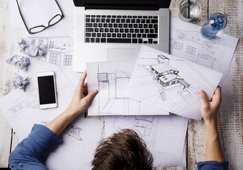Architect working at desk with laptop, looking at sketches - HAPF000380