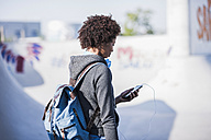 Young woman with backpack and cell phone outdoors - UUF007238