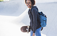 Happy young woman with skateboard listening to music - UUF007259
