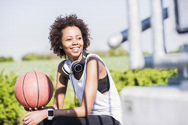 Smiling young woman holding basketball - UUF007283
