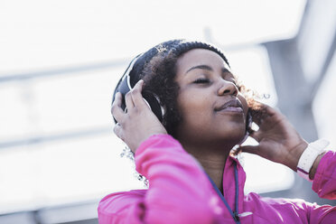 Young woman wearing headphones outdoors - UUF007289