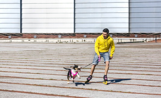 Inline-skater playing with his bull terrier - MGOF001835