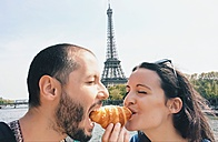 Paris, France, Lovers eating a croissant near the Eiffel Tower - GEMF000907